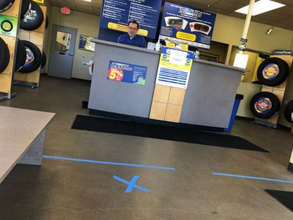 The dealership is enforcing social distancing by asking customers to stand behind floor markings.